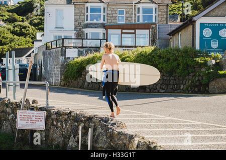 A surfer walking his board, Sennen Cove, Cornwall - Stock Image