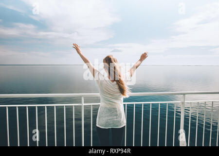 Woman traveler traveling by ferry sea happy raised hands active freedom lifestyle summer weekend vacations outdoor journey - Stock Image