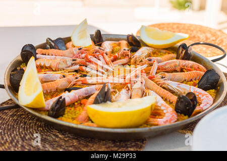 Spanish paella served on the traditional pan, to be enjoyed under a shade on a sunny summer day. - Stock Image