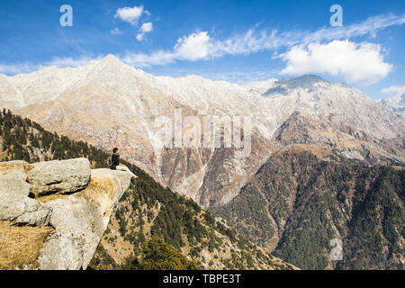 A tourist is sitting on a cliff enjoying the beautiful view of Dhauladhar Mountain ranges during a sunny day. Triund, Dharamsala, Himachal Pradesh - Stock Image