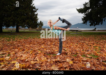 A young women doing yoga at Spanish Bank in Vancouver, British Columbia, Canada - Stock Image