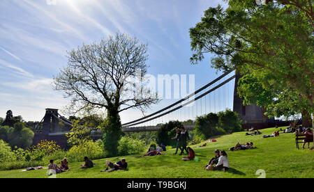 People sunning on grass with view of Bristol Suspension Bridge - Stock Image