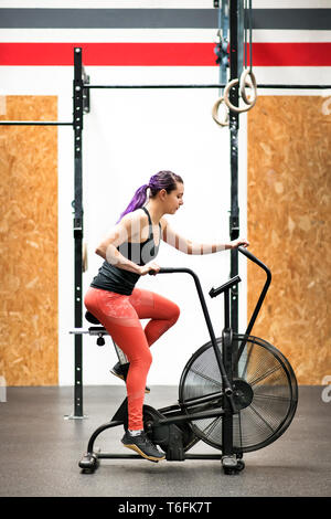 Fit muscular young woman working out on an exercise bike inside a gym in an active lifestyle and health and fitness concept in a side view - Stock Image
