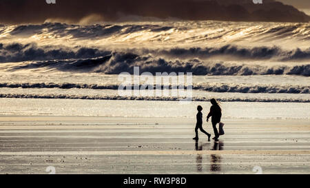 A panoramic view of two people seen in silhouette walking across Fistral Beach in Newquay Cornwall. - Stock Image