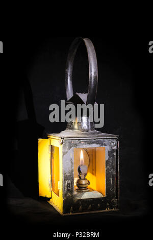 Old railroad petrol lantern with fire inside - Stock Image