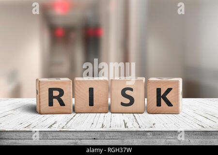 Risk sign on a wooden desk with red lights on in a hallway - Stock Image