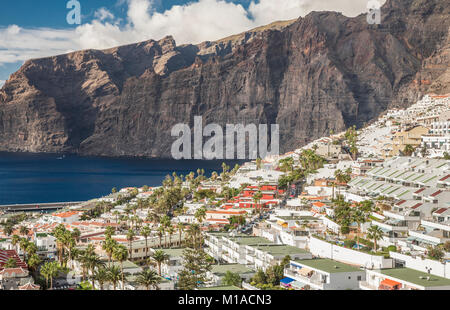 The tourist resort town of Los Gigantes, Tenerife, Canary Islands, with the famous giant cliffs from which the town - Stock Image