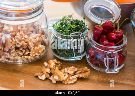 Close up of fresh healthy food ingredients like nuts and chiully pepper - piece of tqable in the kitchen - restaurant and fresh fruits and vegatables - Stock Image