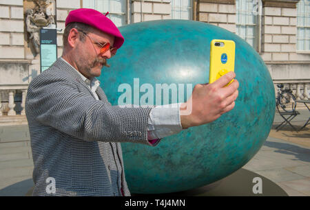 London, UK. 17th April, 2019. A giant bronze egg sculpture, 'Oeuvre', by Gavin Turk (pictured), is unveiled at Somerset House. The bronze egg is intended as a starting point and inspiration for photographer's around the world to Collaborate with Gavin on an ambitious public installation for Photo London, titled 'Gavin Turk - Portrait of an Egg'. All that is required to take part is a digital photographic device with which to record their own 'Portrait of an Egg. Credit: Malcolm Park/Alamy Live News. - Stock Image