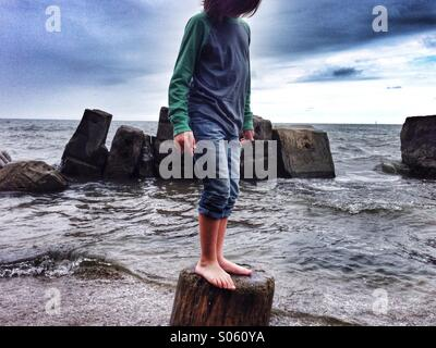 Boy on driftwood at the beach on Lake Erie, Ohio. - Stock Image