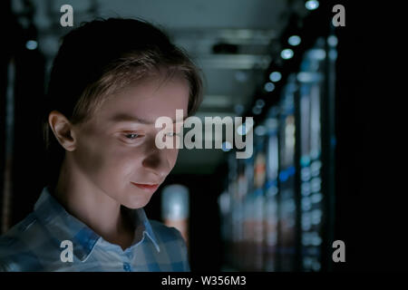 Light from electronic kiosk illuminated woman face - Stock Image