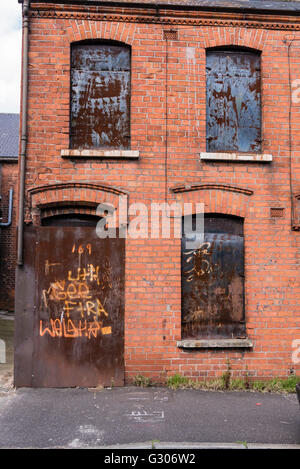 Derelict house boarded up with steel plates. - Stock Image
