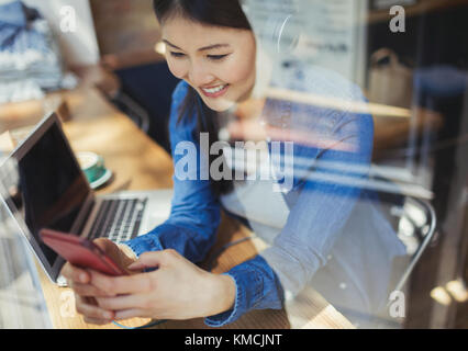 Smiling young woman listening to music with headphones and texting with cell phone at laptop in cafe window - Stock Image
