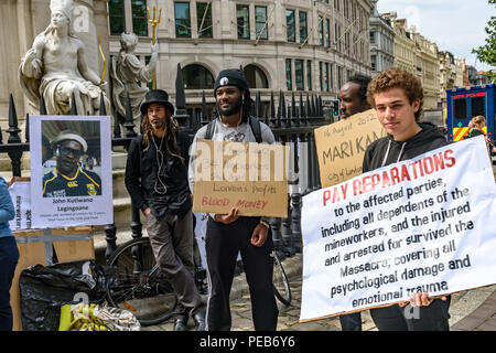 London, UK. 13th August 2018. Three days before the 6th anniversary of the massacre when 34 striking miners were shot dead by South African police at Lonmin's Marikana platinum mine, protesters meet outside St Paul's Cathedral for a tour of the City of London visited investors, insurers and shareholders profiting from the violence against people and nature in Marikana and heard about the colonial roots of the huge wealth of the City. Credit: Peter Marshall/Alamy Live News - Stock Image