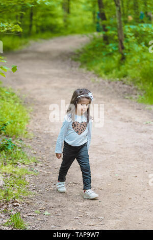 Adorable four years old cute little girl walks on a rural road in  near a pod or lake at park in a sunny day - Stock Image
