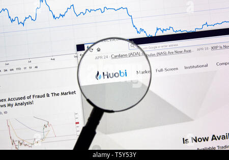 MONTREAL, CANADA - APRIL 26, 2019: Huobi cryptocurrency digital assets exchange logo and home page on a laptop screen under magnifying glass. - Stock Image