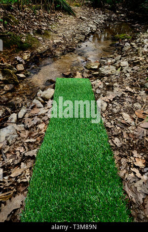Artificial green plastic grass carpet by the river - Stock Image