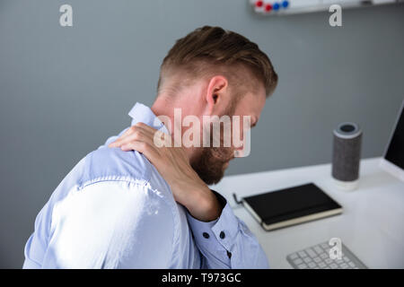 Businessman Suffering From Neck Pain At Desk - Stock Image