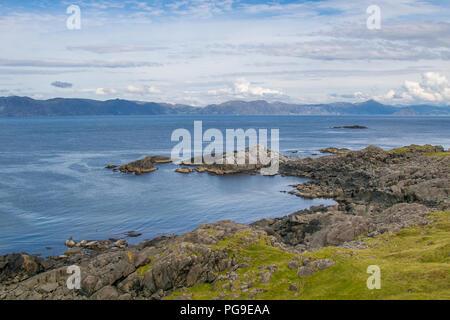 Coastal Norway. Serene scene of natural beauty. Rocky coastline, blue cloudy sky, mountains on horizon. - Stock Image