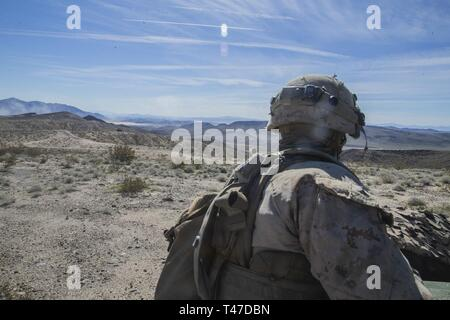 U.S. Marine Lance Cpl. Sam A. Pooley, a rifleman with 2nd Light Armored Reconnaissance Battalion, 2nd Marine Division scans the valley below during a deployment for training at Fort Irwin, California, March 15, 2019. The Marines of 2d Light Armored Reconnaissance Battalion participated in National Training Center 19-05 as the opposing force against the 2nd Armored Brigade Combat Team, 1st Infantry Division. The exercise provided Marines and Sailors an opportunity to sustain training in primary conventional combat operations against a peer competitor. - Stock Image
