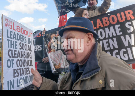 London, UK. 3rd November 2018. Martin Smith of Class War who came to the 'No Demolitions Without Permission' housing protest at City Hall with banners declaring that Labour Councils were the biggest social cleansers in London and 'Labour, Labour Home Snatchers! Even Worse Than Maggie Thatcher', pointing out that it was largely Labour councils who were demolishing council estates so that developers could replace council houses with large numbers of properties sold at high market prices and a miserably small number of homes at social rent, promoting schemes which cut by thousands the number of c - Stock Image