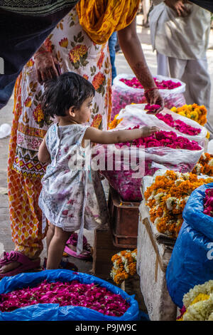Cute little Indian girl with a woman looking at flowers in a stall in Old Delhi, India - Stock Image