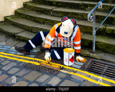 A workman hand repainting double yellow lines on the road in Staithes North Yorkshire in preparation for the coming busy tourist season - Stock Image