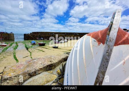 Rowing boat upside down in the Cornish fishing village of Mousehole,Cornwall,England,UK - Stock Image