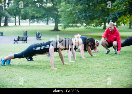 A group of women doing press-ups and exercises in a public park early in the morning on a bootcamp with a male fitness - Stock Image