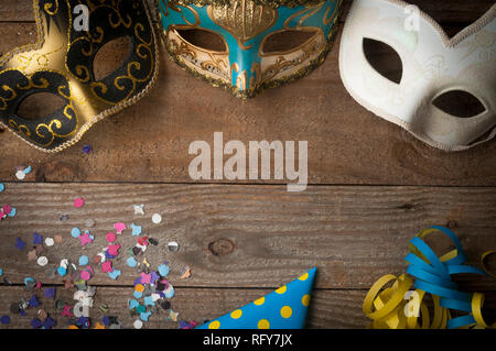 Mardi gras masks on wooden table with streamers and confetti - Stock Image