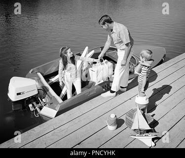 1970s FAMILY OF THREE FATHER MOTHER SON LOADING PICNIC COOLERS TOYS AND WATER SKIS INTO OUTBOARD MOTOR BOAT DOCKSIDE - b24696 HAR001 HARS RIVER NOSTALGIA OLD FASHION 1 JUVENILE BALANCE SAFETY TEAMWORK VACATION SONS FAMILIES JOY LIFESTYLE FEMALES MARRIED RURAL SPOUSE HUSBANDS HOME LIFE COPY SPACE FULL-LENGTH LADIES PERSONS SCENIC MALES RISK CONFIDENCE TRANSPORTATION FATHERS B&W LOADING TIME OFF HAPPINESS HIGH ANGLE ADVENTURE LEISURE AND GETAWAY DADS EXCITEMENT EXTERIOR KNOWLEDGE RECREATION MOTOR BOAT INTO OF HOLIDAYS CONNECTION ESCAPE STYLISH CARRIERS COOLERS DOCKSIDE COOPERATION JUVENILES - Stock Image