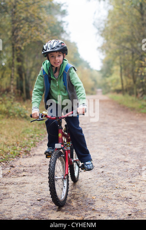 Boy in green jumper and cycling helmet rides his red bike on a forest trail  in Moors Valley Country Park - Stock Image