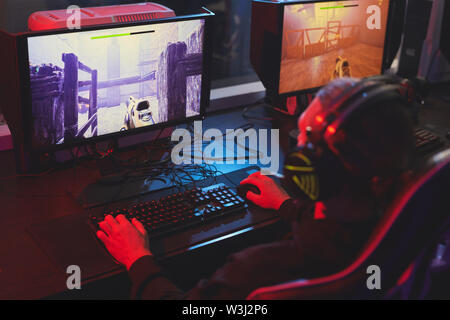 Rear view of unrecognizable man in headset sitting at table and playing arcade shooting game - Stock Image