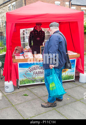 Man customer in Saltburn Farmers Market looking at a display of sausages from Free Range outdoor reared pigs - Stock Image