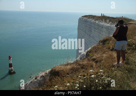 Beachy Head, UK - July 14 2018: Tourist seen on Beachy Head cliff overlooking the Beachy Head Lighthouse 162 metres  below  on a hot summers day on 14 July 2018. Temperatures raised to 27 degrees and is expected to stay high for another month. The cliff, the highest chalk sea cliff in Britain rises to 162 metres above sea level and unfortunately one of the most notorious suicide spots in the world. Credit: David Mbiyu - Stock Image