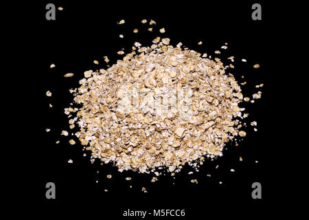 Rolles oats on a black background - Stock Image