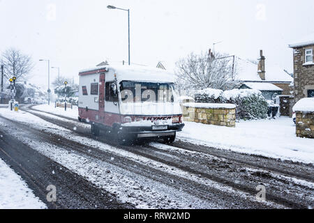 Bradford on Avon, UK, February 1st 2019: A Hymer campervan driving through snowy conditions Campervan out driving in snowy conditions with slush cover - Stock Image