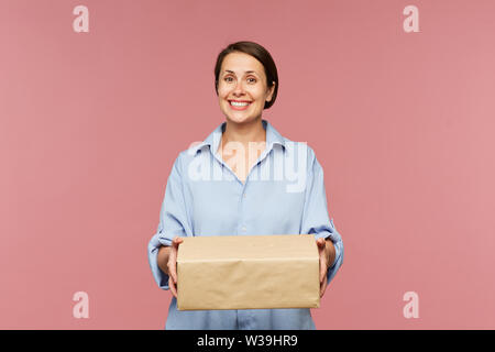 Young happy client of online shop with big packed box looking at you in isolation - Stock Image