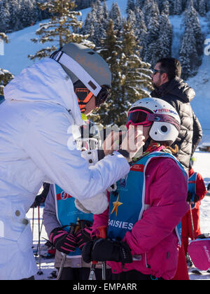Mother and small child in skiing clothes preparing for a skiing lesson with slope  behind - Stock Image