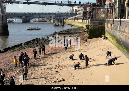 A view of schoolchildren school group mudlarking and playing in sand beach by the Millennium Bridge and River Thames in London England UK KATHY DEWITT - Stock Image