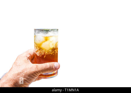 Hand holding a rum and coke cocktail in glass with ice - Stock Image