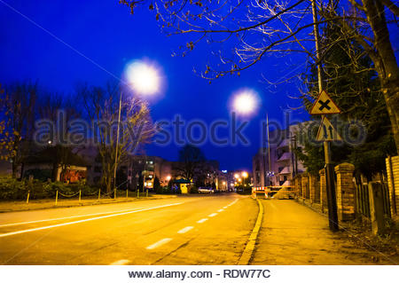 Poznan, Poland - November 16, 2018: Street with construction area and apartment blocks on the Stare Zegrze area by night. - Stock Image