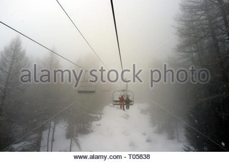 In cloudy snowy weather, skiers take the chairlift at the ski resort in Sainte-Foy-Tarentaise, Auvergne-Rhône-Alpes region in south-eastern France. - Stock Image