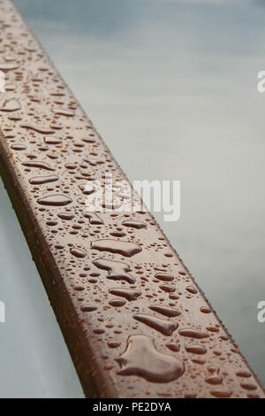 Olden, Norway - 8 August 2018: Raindrops on a deck railing on a cruise ship sailing the Fjord to Olden. The village of Olden at the end of the Nordfjord on 8 August 2018. The village of about 500 inhibitions engage in agriculture, fruit growing and manufacture for tourism. Photo: David Mbiyu - Stock Image