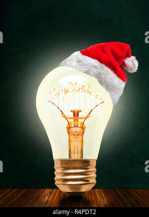 Glowing light bulb wearing Santa hat with Merry Christmas message on chalkboard background with copy space. Glowing Christmas and a bright New Year ah - Stock Image