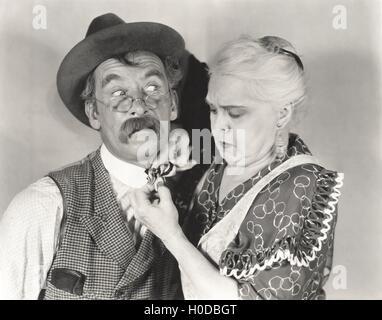 Woman straightening bewildered man's bow tie - Stock Image