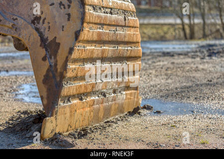 Close up view of attached excavator bucket and bucket teeth resting on ground outdoors - Stock Image