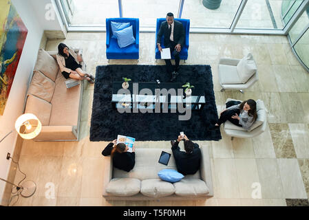 Business people talking in hotel lobby - Stock Image