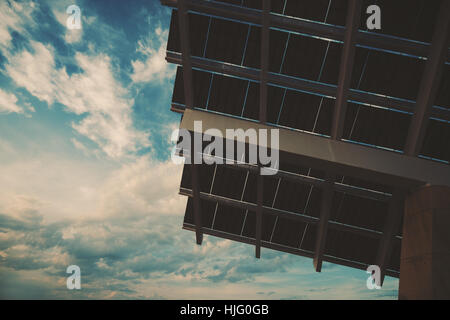 Close-up fragment of modern hi-tech solar photovoltaic panel with empty space for your message on the left on sky, - Stock Image