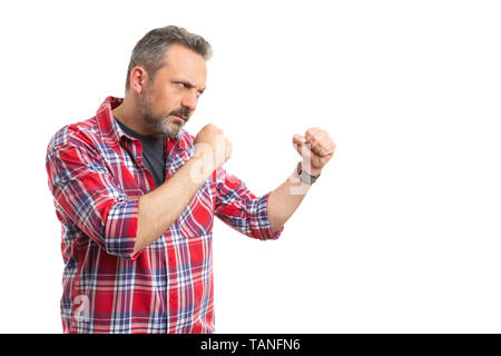Angry man getting ready to fight with copyspace holding fists isolated on white studio background - Stock Image